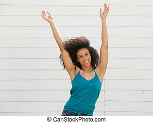 Portrait of a joyful young woman with arms up in the air