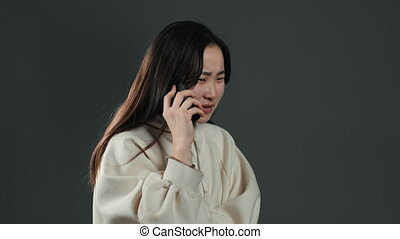 Woman with asian appearance sort things out, swears with somebody by mobile phone. Girl nervous, expresses discontent and resentment