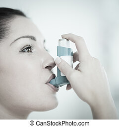 Woman with asthma using the inhaler - Woman using an asthma...