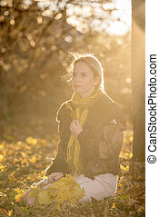 Woman with autumn leaves in the sunset