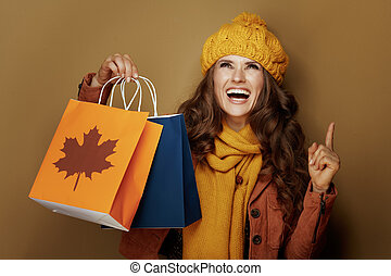 woman with autumn shopping bags pointing up at copy space - ...