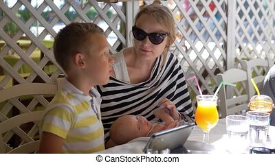 Woman with baby and elder child in cafe on summer day