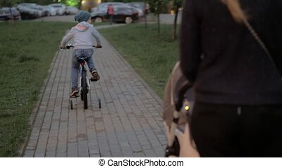 Woman with baby and elder son having outdoor walk in the evening