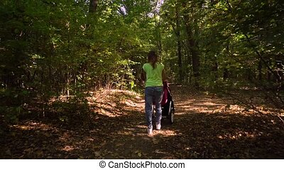 Woman with baby and stroller walking in forest. View from back