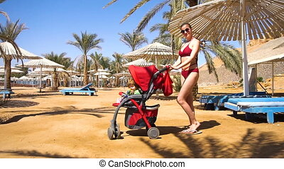 Woman with baby in carriage on the beach