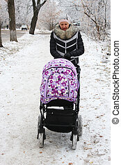 Woman with baby in perambulator walking on the winter road