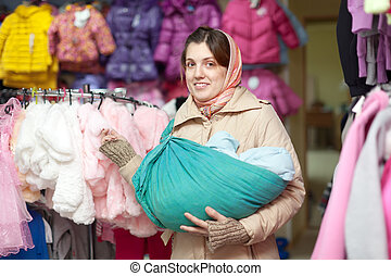 woman with baby in sling at shop