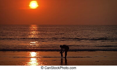 Woman with baby on the beach during sunset