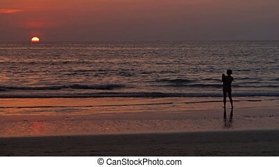 Woman with baby on the beach watching the sunset