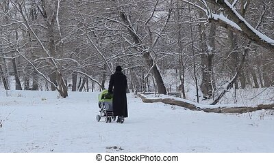 Mother in black winter coat walks with baby stroller on the snowy park alleys.