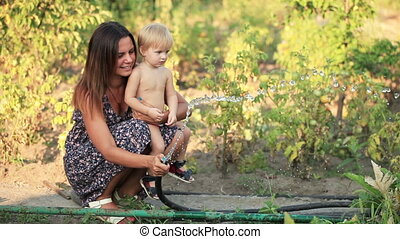 Woman with baby watered - Beautiful girl with a child...