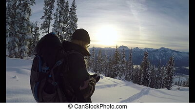 Woman with back pack using her phone on snow covered...