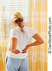 woman with back pain - a woman on the morning after waking ...