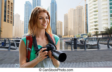 woman with backpack and camera over dubai city - adventure, ...