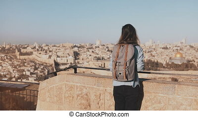 Woman with backpack comes up to Jerusalem panorama. Excited Caucasian tourist looks at ancient old town in Israel. 4K.