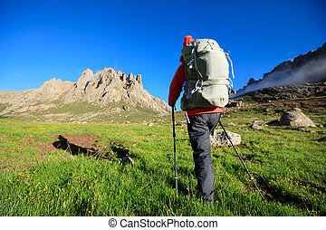 woman with backpack hiking in mountains