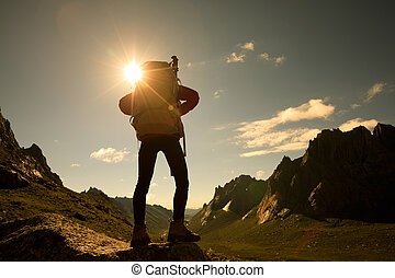 woman with backpack hiking in mountains travel lifestyle