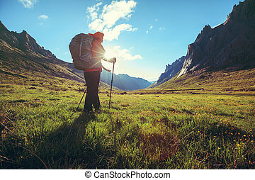 woman with backpack hiking in sunrise high altitude mountains