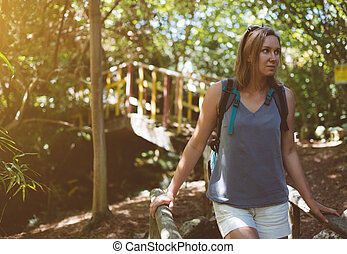 Woman with backpack in the forest.