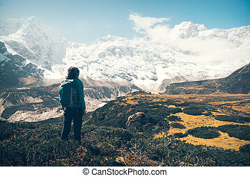 Woman with backpack looking on beautiful mountains