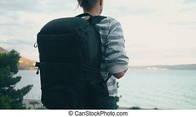 Woman with backpack near the sea coast.
