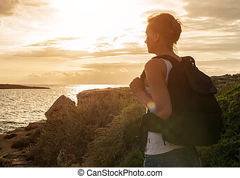 Woman with backpack on the sunset.
