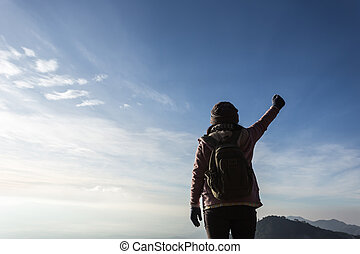Woman with backpack standing on top of a mountain with raised hands