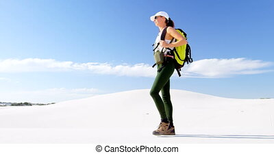 Woman with backpack walking in the desert 4k