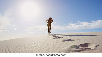 Woman with backpack walking in the desert on a sunny day 4k...