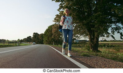 Woman with backpack walking on roadside. Cheerful young...