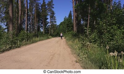 Woman with backpack walking on rural road near forest