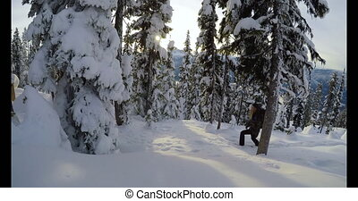 Woman with backpack walking on the snow covered mountain 4k...