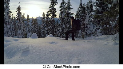Woman with backpack walking on the snow covered mountain 4k