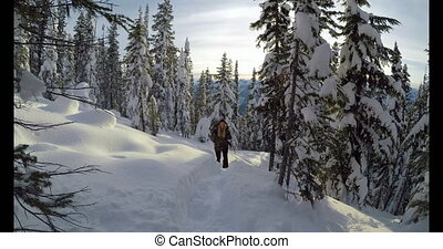 Woman with backpack walking on the snow covered mountain...