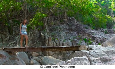 Woman with backpack walking on wooden bridge over river while hiking in mountains. Traveling woman walking on hanging bridge in jungle forest. Summer climbing in mountains.