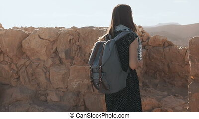 Woman with backpack walks among ancient walls. Attractive...