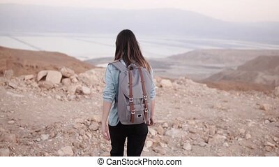 Woman with backpack walks in desert. Slow motion. Young girl...