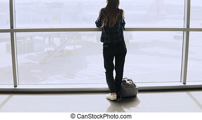 Woman with backpack walks to airport window. Happy successful European passenger girl with smartphone in terminal. 4K.