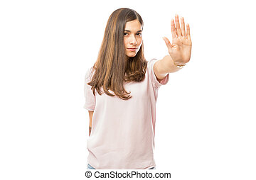 Woman with bad attitude making stop gesture with her palm against white background