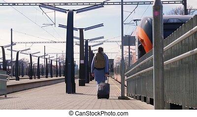 woman with bag walking along railway station - health, ...