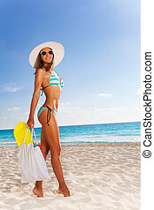 Woman with bag walking to the beach - Young attractive woman...