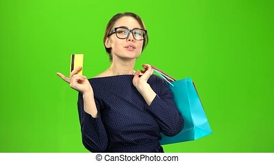 Woman with bags of paper goes shopping with a card in her hands. Green screen