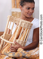 Woman with baguettes in a bakers