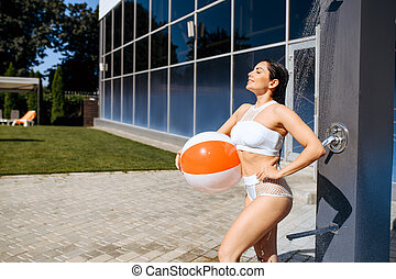 Woman with ball having a shower outdoors on resort