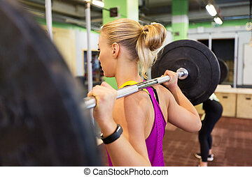 woman with barbell at group training in gym