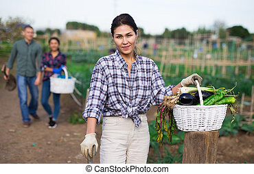 Woman with basket of ripe vegetables on field