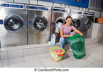Portrait of beautiful woman with baskets of clothes smiling at laundry