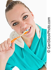 Woman with bathrobe washing her teeth