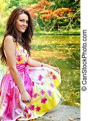 Woman with beautiful colorful dress near lake