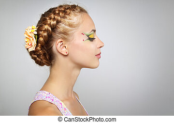 Woman with beautiful hairstyle and creative make-up on light...